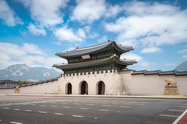 Строб и стена дворца gyeongbokgung с славным небом в наземном ориентире утра сеула, южной кореи. азиатский туризм, историческое здание или традиционная культура и концепция путешествия