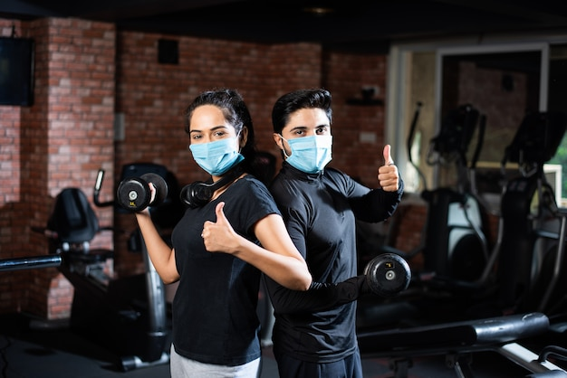 Gym after corona - indian young couple working out in gym post corona outbreak, wears protective face mask