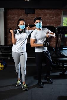 コロナ後のジム-コロナ発生後のジムで運動しているインドの若いカップル、保護フェイスマスクを着用