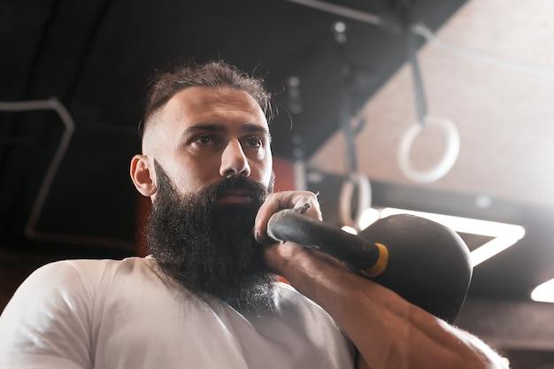 Gym. bearded man training. kettlebell.