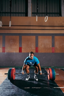 Gym concept with man about to lift barbells