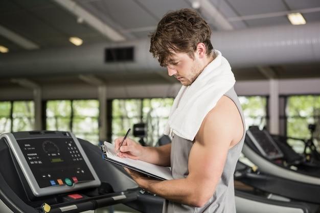 Gym instructor writing on clipboard