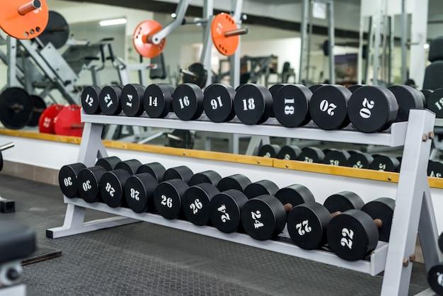 Интерьер тренажерного зала с оборудованием гантелей в рядах