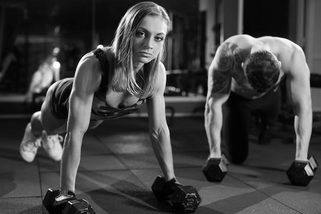 フィットネストレーニングでダンベルを使ったジムの男性と女性の腕立て伏せ筋力プッシュアップ。黒と白