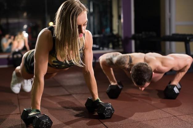 フィットネストレーニングでダンベルとジムの男性と女性の腕立て伏せ筋力プッシュアップ