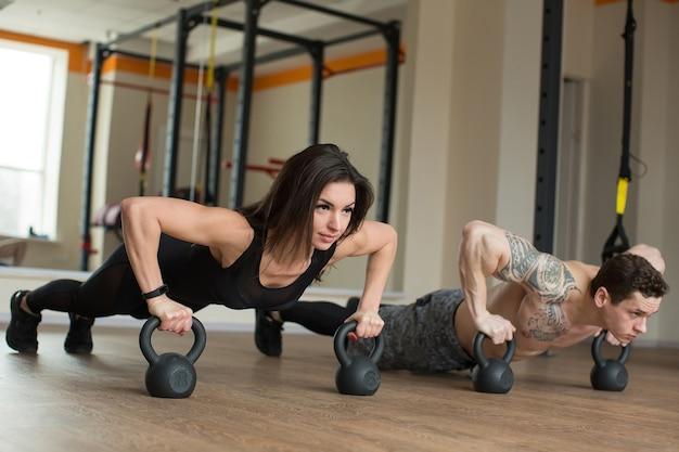 Силовые отжимания мужчины и женщины в спортзале с гирями во время фитнес-тренировки