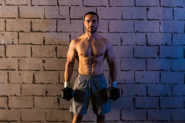 Gym man holding hex dumbbells with muscles