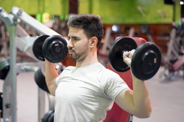 Gym man strength training lifting weights.