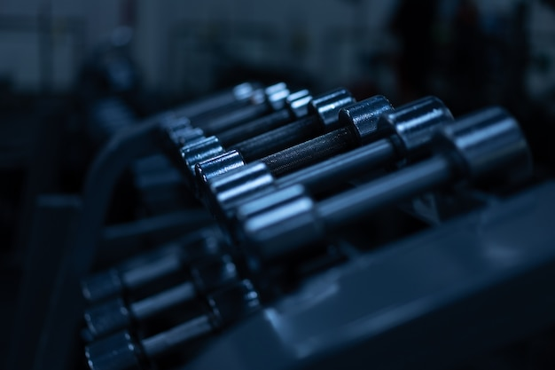 Gym. metal dumbbells in a row sport and fitness concept dark toned horizontal photo