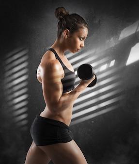 Женщина в тренажерном зале тренирует бицепсы с гантелями