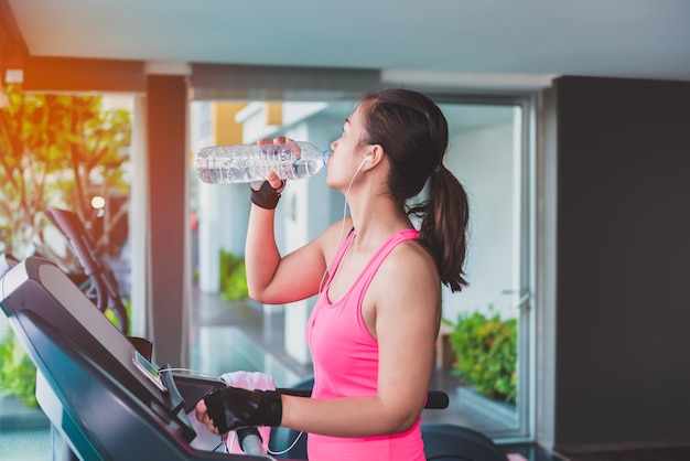 Gym woman working out drinking water by moonwalker fitness machines. asian female fitness model insi