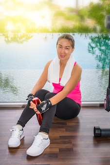 Gym woman working out sitting drinking water at fitness center. asian female fitness model inside in
