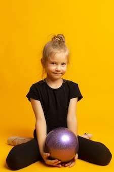 Gymnast girl in black trico full height sits on a half page with a sports ball isolated on a yellow background