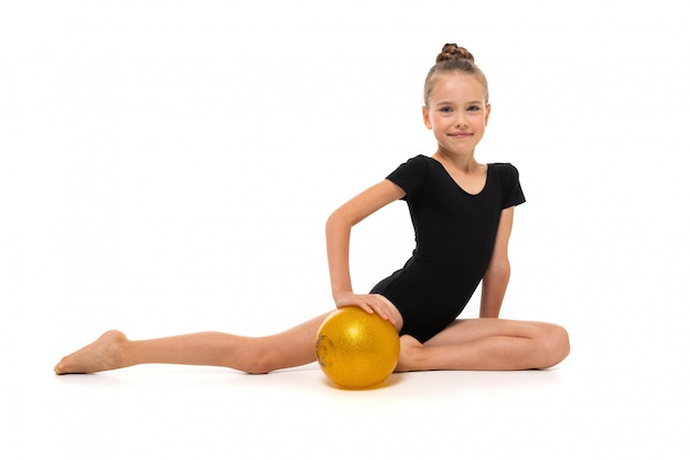 Gymnast girl in black trico full height sits on a half page with a yellow ball