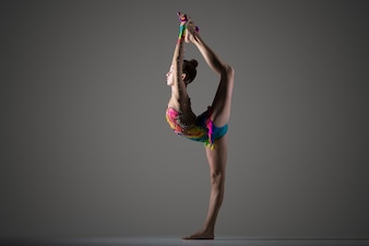 Gymnast girl doing standing backbend with mace