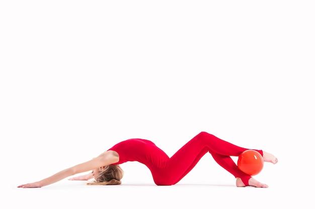 Гимнастка в красном комбинезоне делает упражнение с мячом на белом фоне