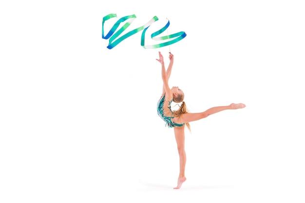 에메랄드 수영복 체조 소녀는 흰색 리본으로 운동을 수행