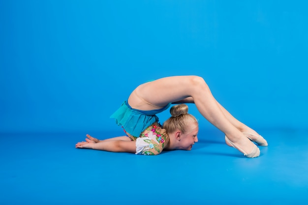 Gymnast girl performs a gymnastic stand with a roll on a blue isolated wall