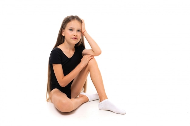 Gymnast girl sitting on the floor on a white background with copy space