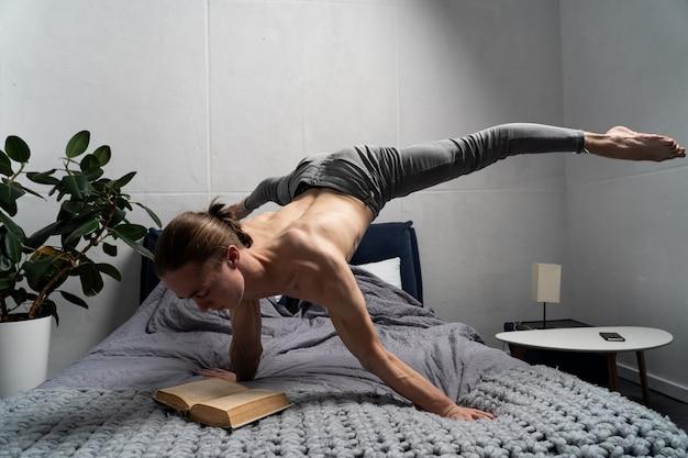 Гимнастка читает книгу и удерживает равновесие на руке в горизонтальном положении