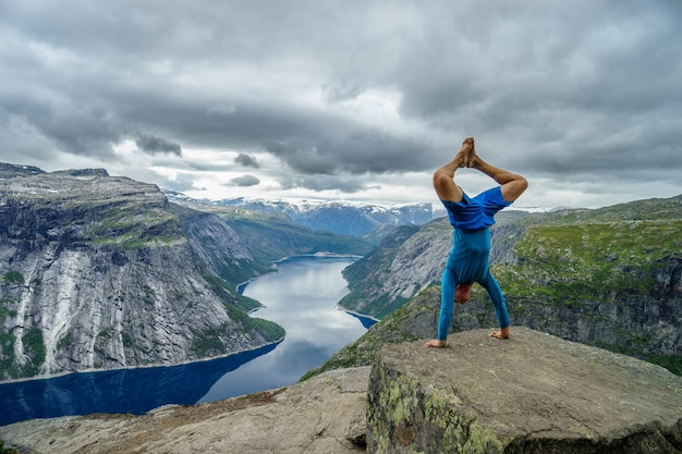 Гимнастка стоит на руках на краю фьорда на фоне возле тролльтунги. норвегия.