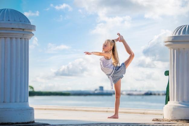 바다와 하늘을 배경으로 제방에 포즈를 취하는 매력적인 금발의 체조 10대 소녀