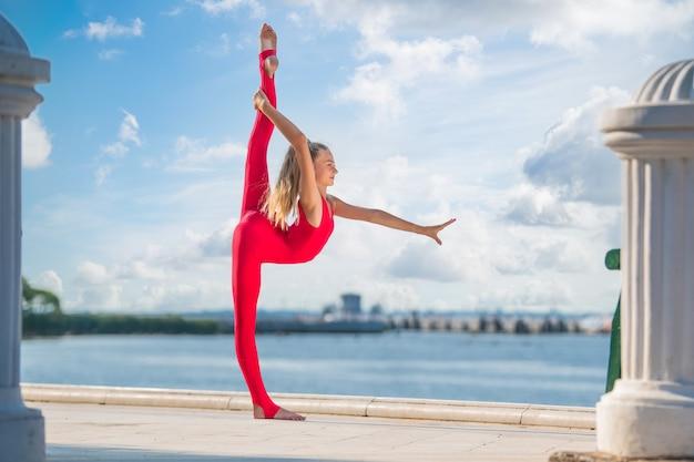 바다와 하늘을 배경으로 제방에 포즈를 취하는 빨간 양복을 입은 체조 10대 소녀