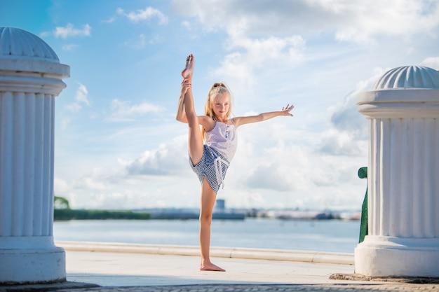 Гимнастка девочка-подросток позирует на набережной на фоне моря и неба