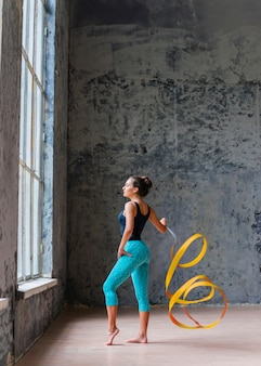 Gymnast woman dancing with yellow ribbon