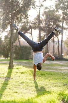 Гимнастический мужчина стойка на руках на одной руке делает акробатическую позу