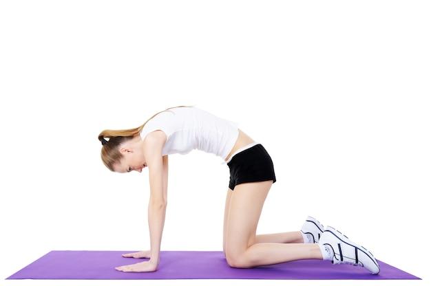 体操用カーペットの上で若い女の子の体操