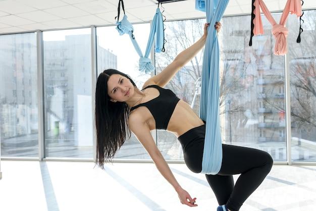 Гимнастика выполняет упражнения на физическое расслабление в гамаке в студии. концепция женского здоровья