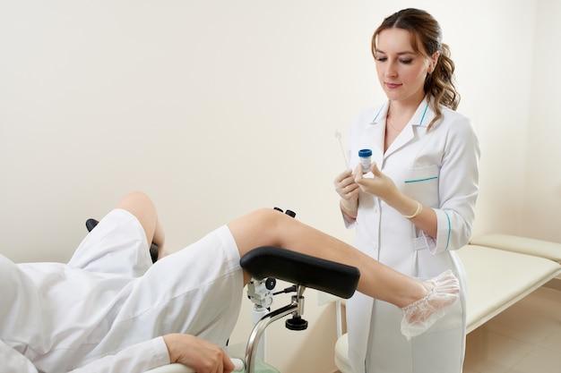 Гинеколог осматривает пациента, сидящего на гинекологическом кресле