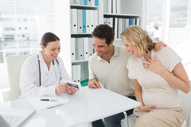 Gynaecologist and expectant couple looking at reports