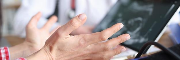 産婦人科医がタブレット画面で女性に胚の超音波スキャンを実演