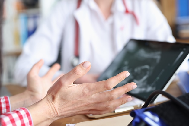 Gynecologist demonstrates embryo ultrasound scan to woman on tablet screen