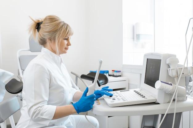 婦人科医は患者の診断のために超音波装置を準備します