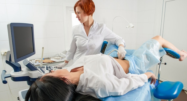 Gynecologist doing ultrasound scanning for pregnant woman