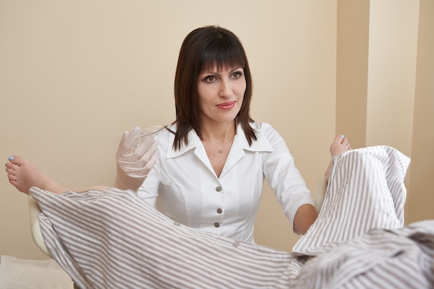 患者の膣検査のために鏡を持っている産婦人科医