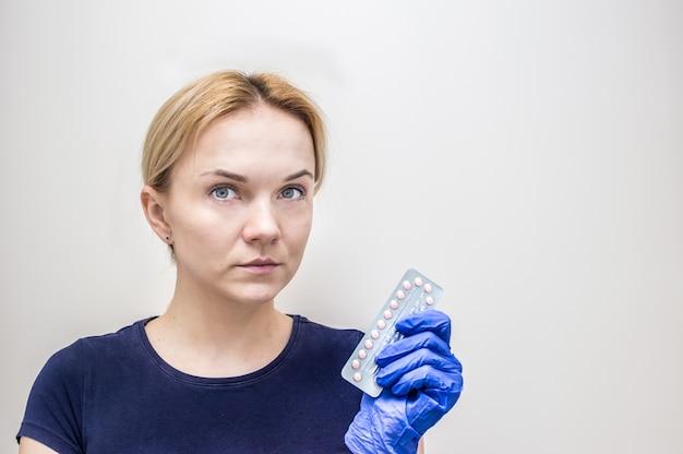 産婦人科医は彼の手に経口避妊薬のパックを持っています