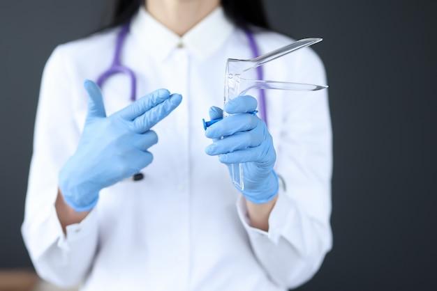 産婦人科医は女性を検査するための器具を持っています。婦人科検査の概念