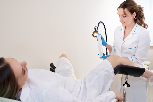Gynecologist using vaginal swab for std testing. woman in gynecological chair