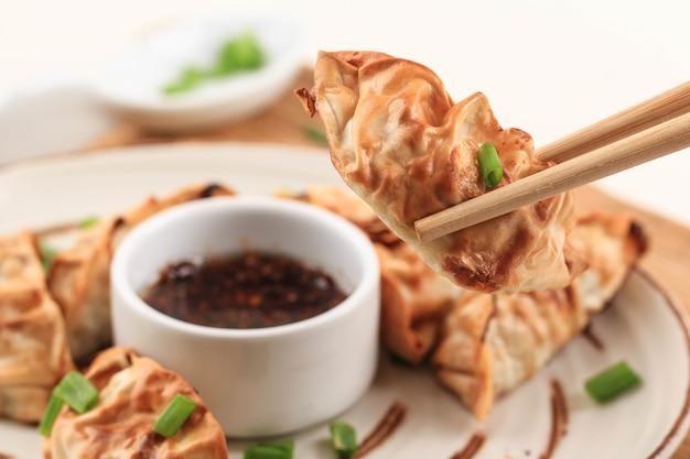 白い木製の背景の上に箸とネギを添えた茶色のセラミックジャパンスタイルプレートで提供されるソース付きgyozaアジアンポットステッカー。油を使わないエアフライヤー調理。