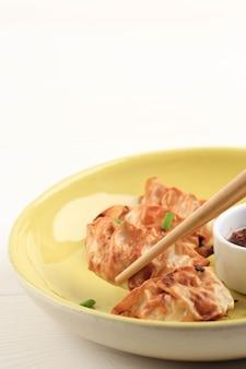 白い木製の背景の上に箸とネギと黄色いセラミックプレートで提供されるソースとgyozaアジアのポットステッカー。油を使わないエアフライヤー調理。