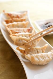 Gyoza and chopsticks on white plate