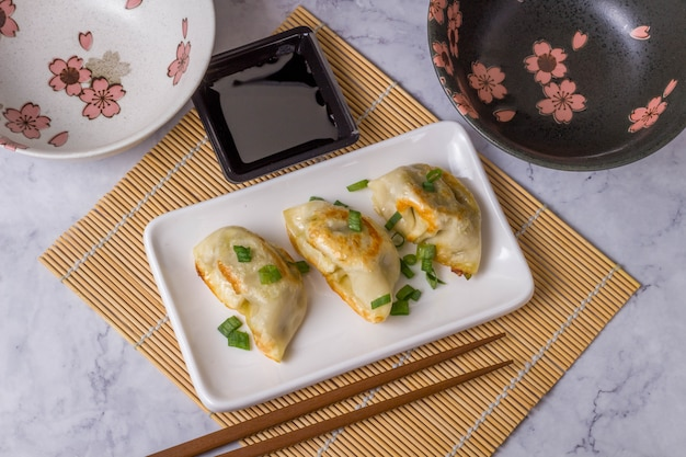 Gyoza is traditional asian cuisine dish with pasta with stuffing of beef, beef of pork or vegetables