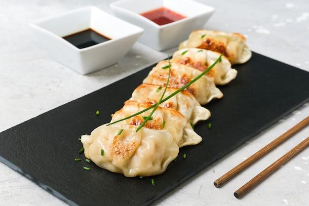 Японские пельмени гёдза с соевым соусом. азиатская кухня. типичная еда японская китайская корейская. доставка на вынос