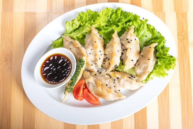 Gyoza on a plate, with herbs and sauce. for any purpose.