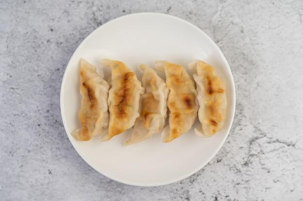 Gyoza in a white dish.