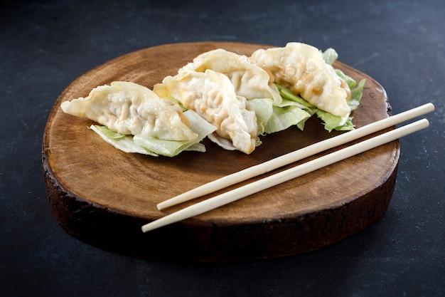 Гёза подается в черной тарелке на деревянном бревне, с палочками для еды и черным фоном
